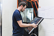 Man operating machine in industrial factory - DIGF03152