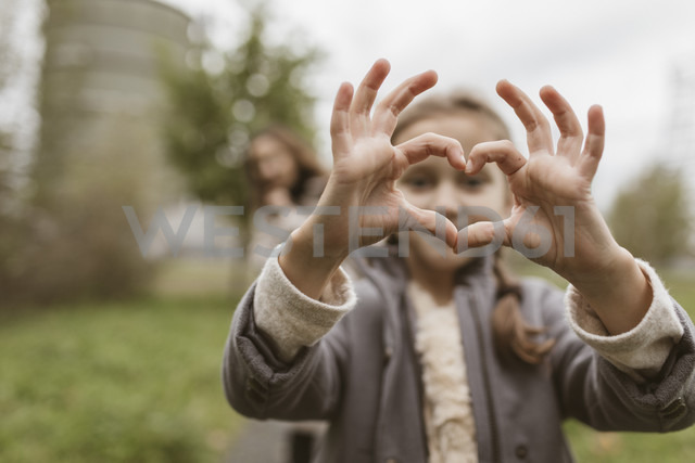 Girl shaping hands to a heart - KMKF00049