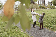 Mother and little daughter dancing together on walkway in autumn - KMKF00052