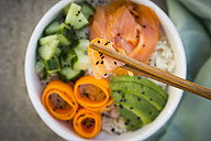 Sushi-Bowl with salmon, cucumber, avocado, rice and carrot, salmon and chopsticks in the foreground - LVF06387