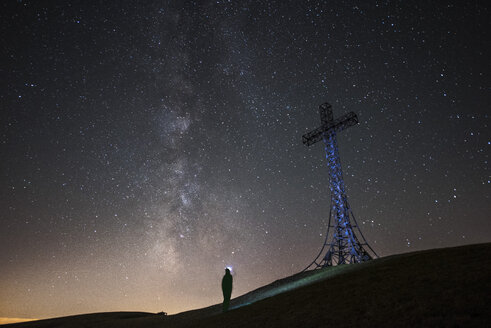 Italy, Marche, silhouette of man looking at summit cross on Monte Catria at night - LOMF00664