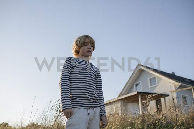 Portrait of serious blond boy against blue sky - KMKF00055