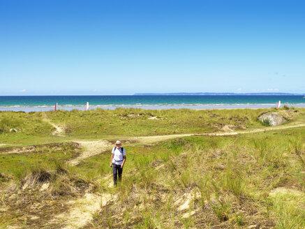 France, Bretagne, Active senior hiking on the beach of Treguer - LAF01930