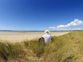 France, Bretagne, Senior man taking a break on the beach, sitting on a dune - LAF01933