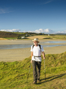 France, Bretagne, Active senior hiking on the beach of Treguer - LAF01936