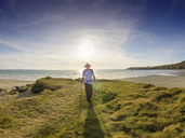 France, Bretagne, Active senior hiking on the beach of Treguer at sunset - LAF01939