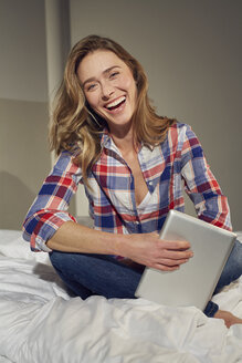 Portrait of laughing woman sitting on bed with tablet - PNEF00255