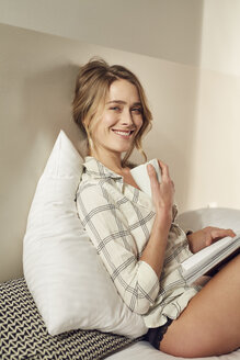 Portrait of smiling woman sitting on bed with coffee mug and magazine - PNEF00261
