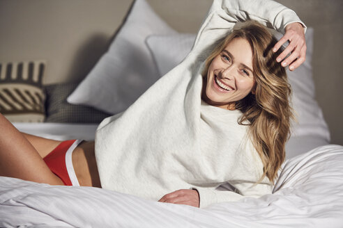 Portrait of laughing woman lying on bed - PNEF00267
