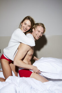 Portrait of happy couple on bed - PNEF00270