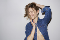 Portrait of laughing woman wearing fully unbuttoned denim shirt - PNEF00279