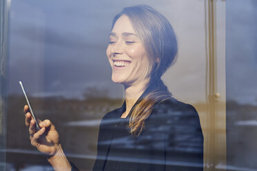 Portrait of laughing businesswoman behind windowpane looking at cell phone - PNEF00282