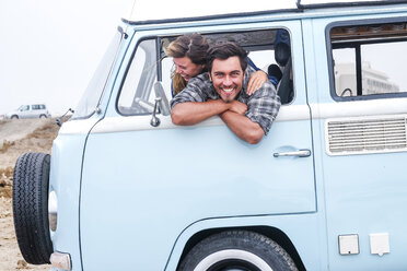 Spain, Tenerife, portrait of laughing man and his girlfriend leaning out of car window of camper - SIPF01834
