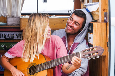 Young couple in love with guitar in a van - SIPF01837