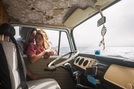 Spain, Tenerife, young couple in love with van near the coast - SIPF01846