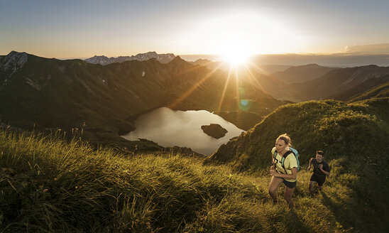Germany, Allgaeu Alps, man and woman running on mountain trail - MALF00002