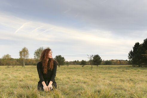 Redheaded young woman crouching on a meadow in autumn - FCF01295