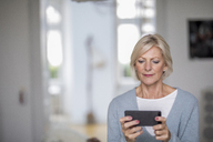 Portrait of senior woman at home looking at cell phone - FMKF04611