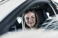 Smiling young woman in car - UUF12202