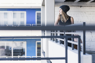 Young woman at apartment building wearing wooly hat - UUF12214