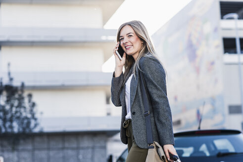 Happy young woman on cell phone in the city - UUF12217