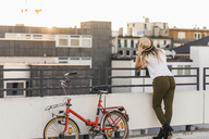 Young woman with bicycle leaning against railing - UUF12232