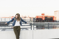 Young woman leaning against railing in the city - UUF12238