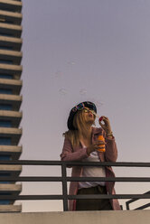 Young woman in the city blowing soap bubbles in the evening - UUF12241