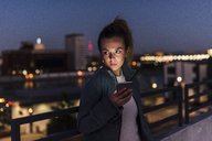 Young woman in the city with cell phone in the evening - UUF12244
