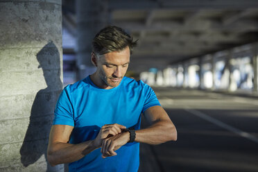 Athlete in the city looking on smartwatch - PNEF00290