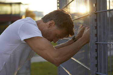 Exhausted athlete leaning against fence - PNEF00293