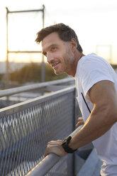 Confident athlete leaning on railing - PNEF00296