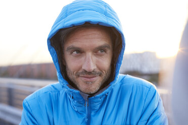 Confident man with hooded jacket in the city - PNEF00302