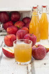 Bottle and glass of apple juice, red apples on wood - LVF06410