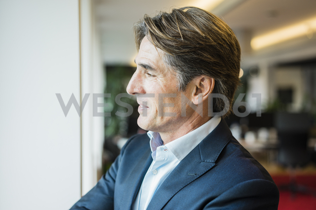Businessman in office looking out of window - JOSF01834