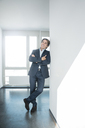 Portrait of smiling businessman standing on office floor - JOSF01840