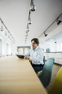 Smiling businessman using tablet at table in office - JOSF01846