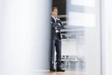 Businessman standing on office floor - JOSF01852