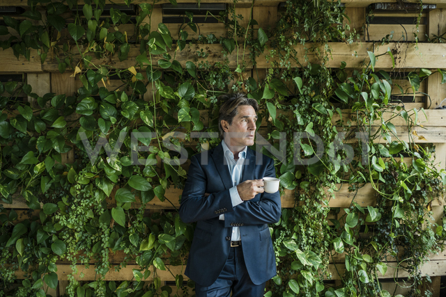 Businessman with cup of coffee in green office - JOSF01858