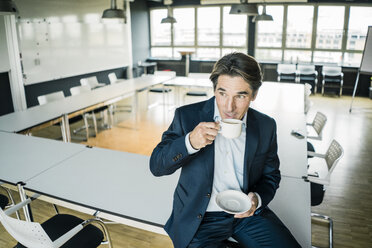 Businessman with cup of coffee  sitting on table in meeting room of an office - JOSF01861