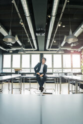 Businessman sitting on table in conference room - JOSF01864