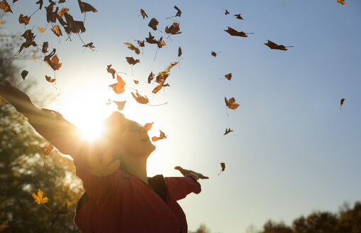 Woman throwing up autumn leaves at backlight - FCF01301