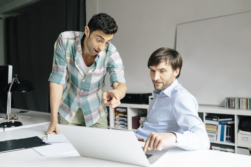 Two businessmen with laptop at desk in office discussing - BMF00848