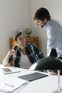 Two happy businessmen with laptop at desk in office discussing - BMF00854