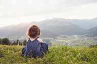 Austria, Tyrol, back view of little girl sitting on Alpine meadow looking at view - RBF06098