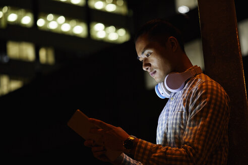 Portrait of young man in the city using tablet at night - JRFF01479