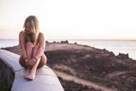 Spain, Tenerife, laughing blond woman sitting on a wall near the sea at sunset - SIPF01855