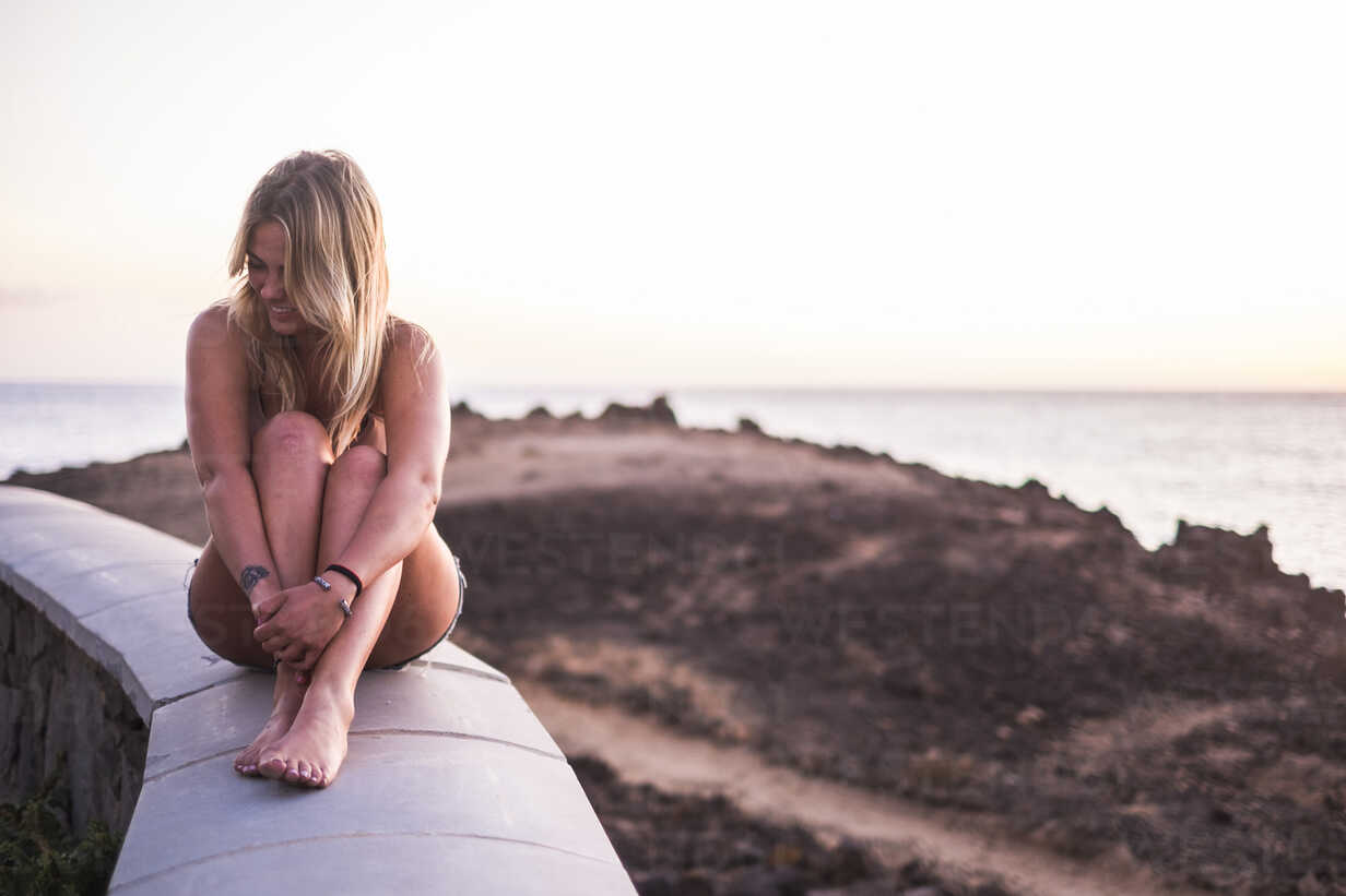 Spain, Tenerife, laughing blond woman sitting on a wall near the sea at sunset - SIPF01855 - Simona Pilolla/Westend61