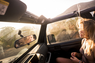 Blond woman with blowing hair sitting in car at sunset - SIPF01858