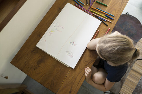 Little girl sitting at table drawing with crayons - SBOF00854